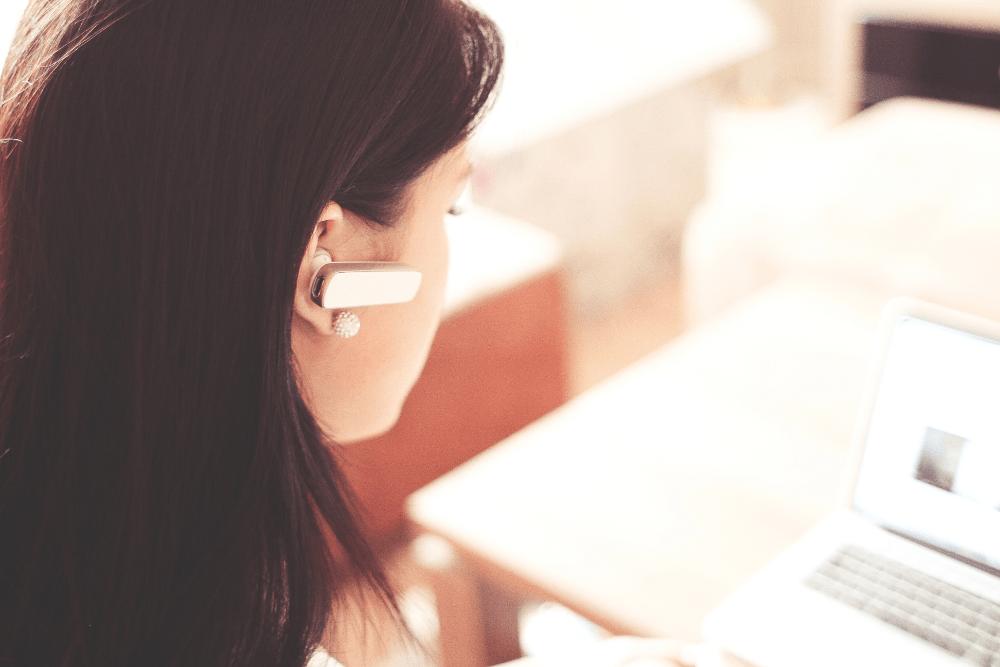 Frau am Schreibtisch, die spricht mit Kunden über Telefon-Headset